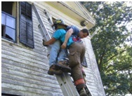 Fireman carrying other man down a ladder