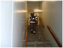 Fireman walking down staircase with hose