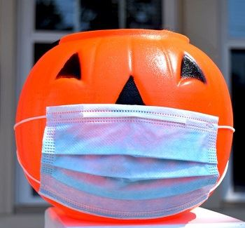halloween pumpkin trick-or-treat basket wearing a face mask