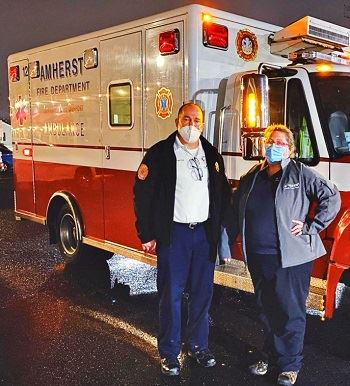 Two town staff members stand in front of ambulance with masks on