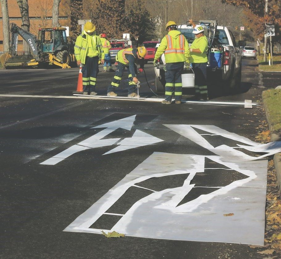 crews painting lines on the roadway